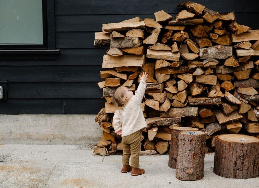 Child-standing-near-firewood