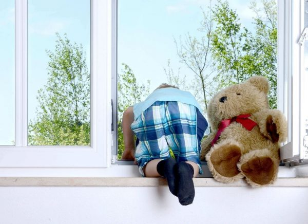 child with teddybear looking outside window